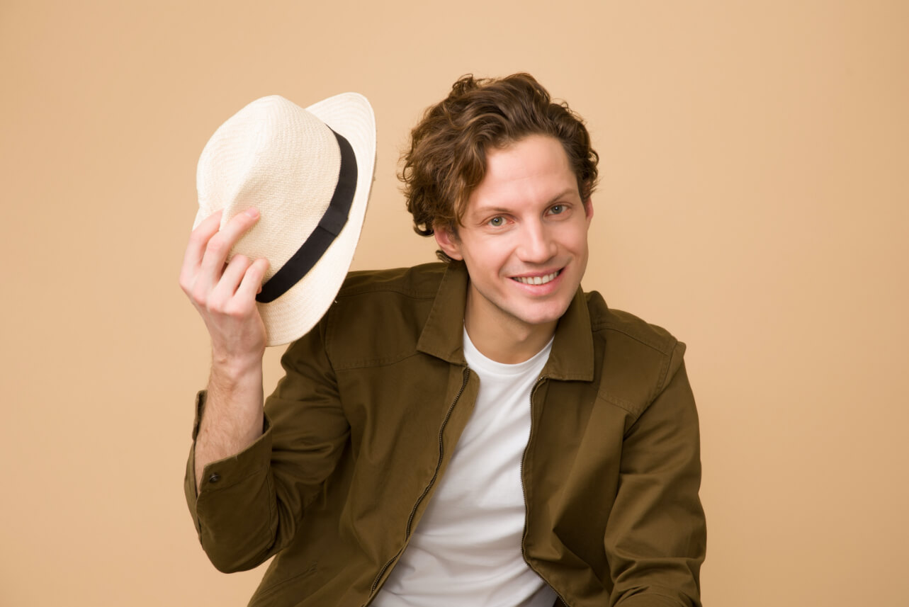 Young handsome male smiling at the camera while taking his hat off